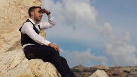 Individuo elegante hermoso que se sienta en las rocas y los pares en la distancia chipre Paphos metrajes