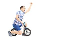 Individuo emocionado que monta una pequeña bicicleta y que gesticula felicidad Imagen de archivo libre de regalías