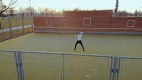 Individuo enérgico joven, un bailarín de la calle en pantalones negros y un suéter blanco, realizando los movimientos hermosos en metrajes