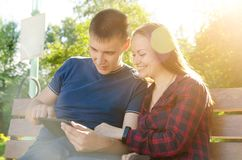 Individuo en camiseta azul y la muchacha en mirada de la camisa de tela escocesa en las fotos que fueron enviadas por los amigos  imagen de archivo libre de regalías