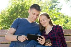 Individuo en camiseta y muchacha azules en camisa de tela escocesa solucionar problemas en la tableta fotografía de archivo libre de regalías