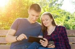 Individuo en camiseta y muchacha azules en un juego del juego de la camisa de tela escocesa en la tableta imagenes de archivo