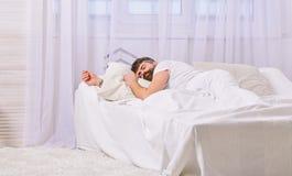 Individuo en cara tranquila que duerme en las hojas blancas, almohada Concepto de la siesta y de la siesta Sirva la colocación en imagen de archivo libre de regalías