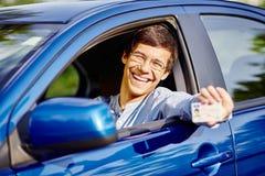 Individuo en coche con el carné de conducir Foto de archivo