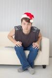 Individuo en el casquillo de la Navidad que tiene mirada fija con los ojos abiertos Fotografía de archivo