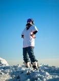 Individuo en el engranaje de la snowboard que se coloca en una montaña Imágenes de archivo libres de regalías
