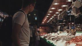 Individuo en el marcador que elige los mariscos metrajes