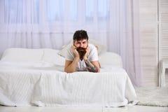 Individuo en la cara tranquila que pone en el borde de la cama en las hojas blancas Sirva la colocación en la cama, cortinas blan Fotografía de archivo