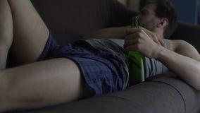 Individuo en los boxeadores y el top sin mangas que dormitan en el sofá, botella de cerveza en su mano, alcoholismo almacen de video