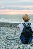 Individuo en sombrero y con la mochila que se sienta en la playa contra el contexto del mar y del cielo de la puesta del sol Visi Imagenes de archivo