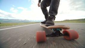 Individuo en su patín del longboard Ciérrese para arriba de longboard y de pie Vista lateral Seguimiento del tiro almacen de metraje de vídeo