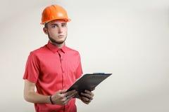 Individuo en un casco protector anaranjado Foto de archivo libre de regalías