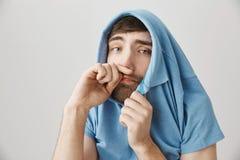 Individuo europeo adulto enfermo y melancólico que oculta en camisa y que mira sin embargo el cuello, limpiando la nariz como si  Foto de archivo