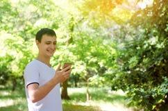 Individuo europeo joven que mira en smartphone y la sonrisa dependencia del teléfono, redes sociales Trabajo sobre el Internet Es Imagenes de archivo