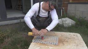 Individuo experto que corta los agujeros en teja usando una amoladora de ángulo con la corona del diamante metrajes