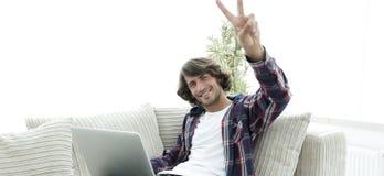 Individuo feliz con el ordenador portátil que se sienta en el sofá y que muestra a su mano un gesto que gana Imagen de archivo libre de regalías