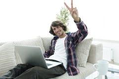 Individuo feliz con el ordenador portátil que se sienta en el sofá y que muestra a su mano un gesto que gana Imagenes de archivo