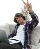 Individuo feliz con el ordenador portátil que se sienta en el sofá y que muestra a su mano un gesto que gana Fotos de archivo