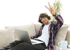 Individuo feliz con el ordenador portátil que se sienta en el sofá y que muestra a su mano un gesto que gana Foto de archivo