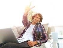 Individuo feliz con el ordenador portátil que se sienta en el sofá y que muestra a su mano un gesto que gana Imagen de archivo