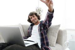 Individuo feliz con el ordenador portátil que se sienta en el sofá y que muestra a su mano un gesto que gana Foto de archivo libre de regalías