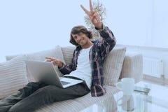 Individuo feliz con el ordenador portátil que se sienta en el sofá y que muestra a su mano un gesto que gana Fotos de archivo libres de regalías