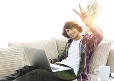 Individuo feliz con el ordenador portátil que se sienta en el sofá y que muestra a su mano un gesto que gana Fotografía de archivo libre de regalías