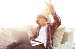 Individuo feliz con el ordenador portátil que se sienta en el sofá y que muestra a su mano un triunfo Imagen de archivo