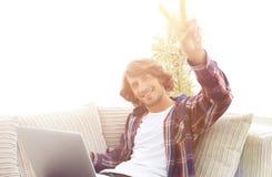 Individuo feliz con el ordenador portátil que se sienta en el sofá y que muestra a su mano un triunfo Imágenes de archivo libres de regalías