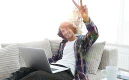 Individuo feliz con el ordenador portátil que se sienta en el sofá y que muestra a su mano un triunfo Fotografía de archivo libre de regalías