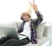 Individuo feliz con el ordenador portátil que se sienta en el sofá y que muestra a su mano un triunfo Fotos de archivo libres de regalías