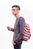 Individuo feliz del inconformista en vidrios con la mochila usando un teléfono elegante a escuchar música Foto de archivo libre de regalías