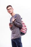 Individuo feliz del inconformista en vidrios con la mochila usando un teléfono elegante a escuchar música Foto de archivo