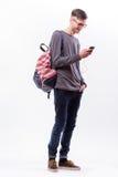 Individuo feliz del inconformista en vidrios con la mochila usando un teléfono elegante a escuchar música con los auriculares Imagen de archivo libre de regalías