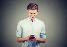 Individuo feliz hermoso que usa un smartphone y una sonrisa Imágenes de archivo libres de regalías