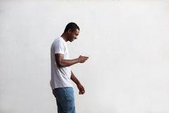 Individuo feliz que camina y que usa el teléfono móvil Foto de archivo libre de regalías