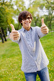 Individuo feliz que muestra los pulgares para arriba en parque Foto de archivo libre de regalías