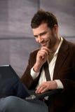 Individuo feliz que sonríe con la computadora portátil Imágenes de archivo libres de regalías
