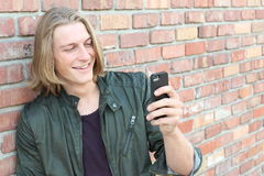 Individuo feliz que usa un teléfono elegante afuera con el espacio para la copia o el texto Imagenes de archivo