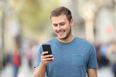 Individuo feliz que usa un teléfono elegante que camina en la calle Fotografía de archivo