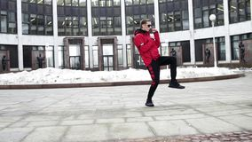 Individuo fresco en danzas rojas de la ropa y de las gafas de sol del deporte al lado de columnas del granito almacen de video