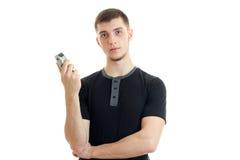 Individuo fuerte joven en una camiseta que sostiene una máquina de afeitar y que mira adelante Fotografía de archivo