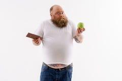 Individuo gordo que toma la decisión de la comida foto de archivo libre de regalías