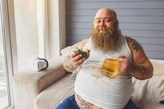 Individuo gordo satisfecho que goza de la comida malsana imagenes de archivo