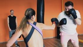Individuo gordo y lucha delgada de la muchacha en guantes de boxeo Taladros de la pérdida de peso individual para el varón grueso metrajes