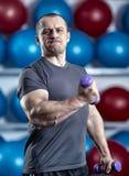 Individuo grande que lleva a cabo ridículo pequeñas pesas de gimnasia Fotos de archivo