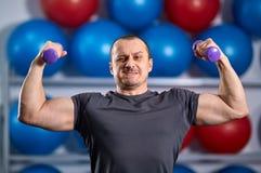 Individuo grande que lleva a cabo ridículo pequeñas pesas de gimnasia Foto de archivo