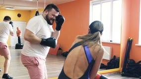 Individuo grueso y una lucha delgada en guantes de boxeo, tonto de la mujer y divertirse Taladros de la pérdida de peso individua almacen de metraje de vídeo