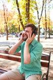 Individuo hermoso divertido con los auriculares en la naturaleza Foto de archivo libre de regalías