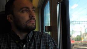 Individuo hermoso en el tren que mira hacia fuera la ventana almacen de video